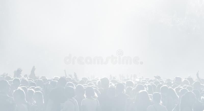 Crowd of spectators at a concert in light blue tonality. High key background with a people on an open playground at a concert. Abstract soft focus image with royalty free stock image