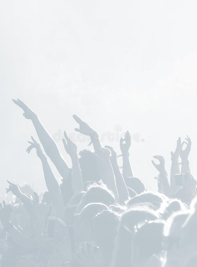Crowd of spectators at a concert in light blue tonality. High key background with a people on an open playground at a concert. Abstract soft focus image with royalty free stock photo