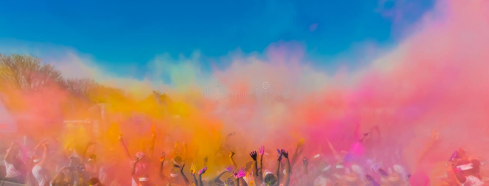 Crowd throwing bright coloured powder paint in the air, Holi Festival Dahan. stock photos