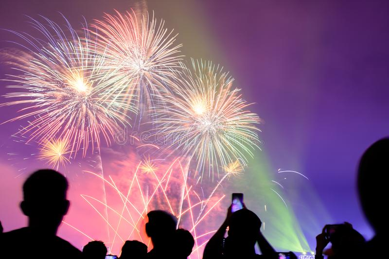 Crowd watching fireworks and celebrating city founded. Beautiful colorful fireworks display in the urban for celebration on dark stock image