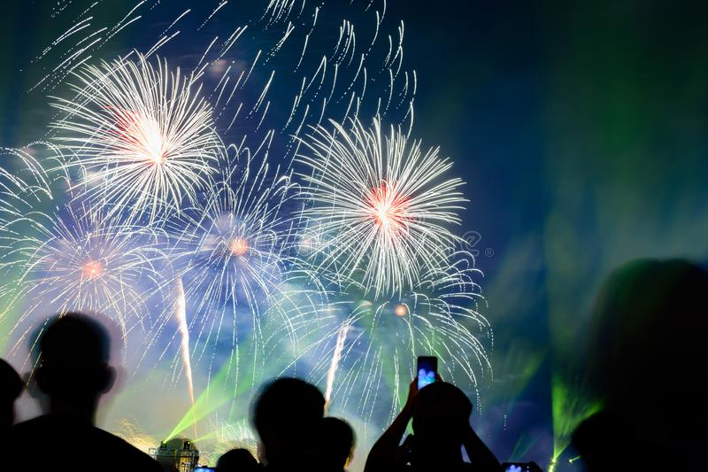 Crowd watching fireworks and celebrating city founded. Beautiful colorful fireworks display in the urban for celebration on dark stock photography