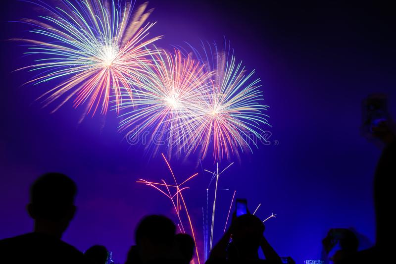 Crowd watching fireworks and celebrating city founded. Beautiful colorful fireworks display in the urban for celebration on dark royalty free stock images