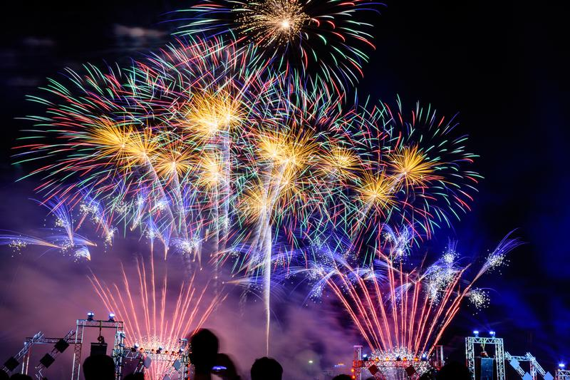 Crowd watching fireworks and celebrating city founded. Beautiful colorful fireworks display in the urban for celebration on dark royalty free stock photography