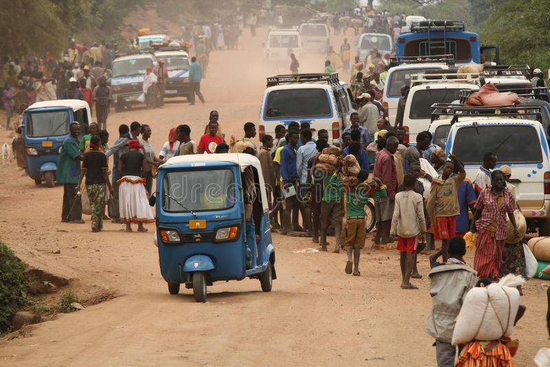 A crowd on the way to the market. A crowd of people goes walking to the market in Gato, in southern Ethiopia. Some carry their goods in vehicles, but the