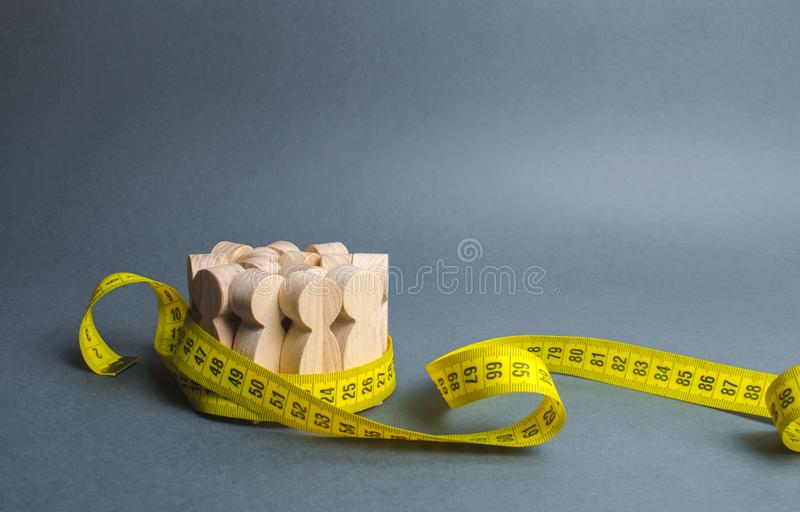A crowd of wooden figures Gripped by measuring tape. Information statistics, measurement of the number, trends of population. Growth. Social Sciences. Promotion royalty free stock photo