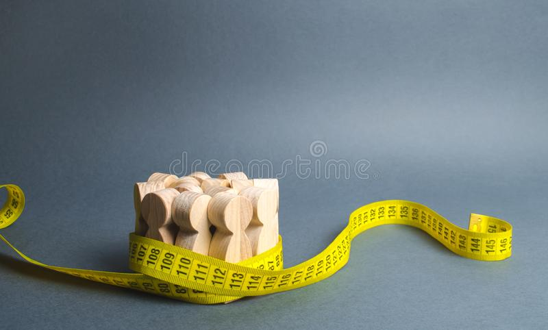 A crowd of wooden figures Gripped by measuring tape. Social Sciences. Promotion of ideas for weight loss, lifestyle. Information royalty free stock photos