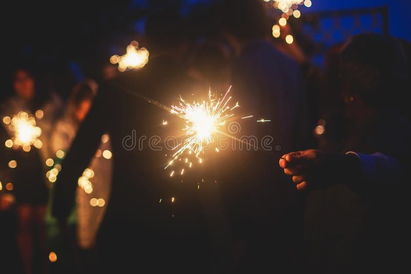 A crowd of young happy people with bengal fire sparklers in their hands during birthday celebration stock images