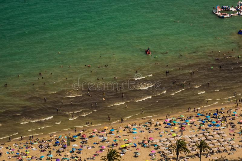 Crowded beach with a blue Mediterranean sea seen from a hill. On a sunny Summer day in August stock photo