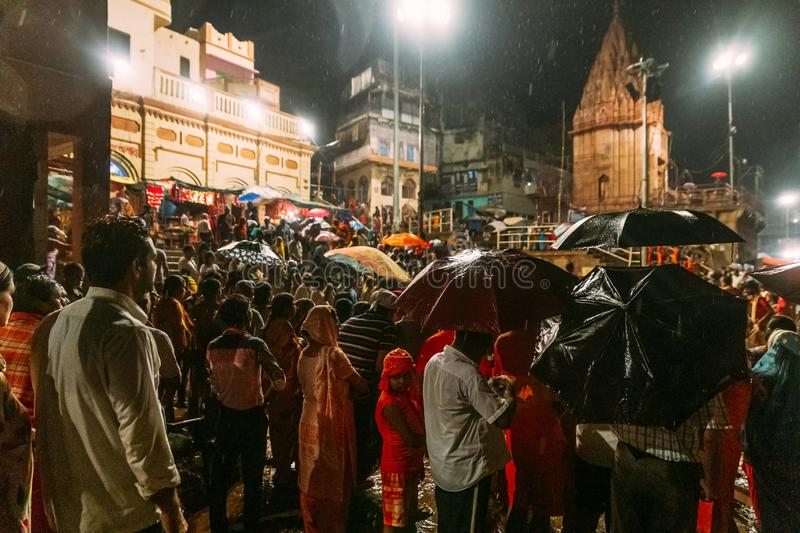 Crowded diversity of people waiting for bless in the rain in Varanasi Ganga Aarti at holy Dasaswamedh Ghat. Crowded diversity of people waiting for bless in the royalty free stock image