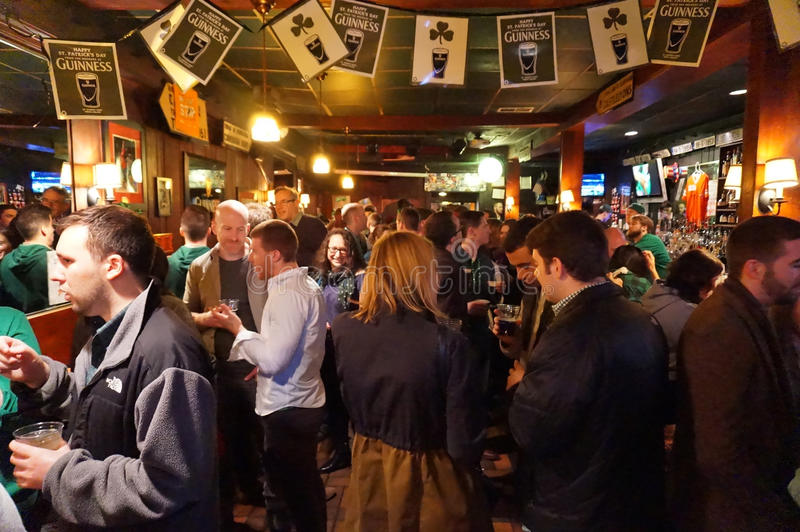 Crowded Irish Pub. Photo of people socializing and drinking inside an irish pub called nanny obriens on saint patricks day on 3/17/17 at night. There is standing stock photo