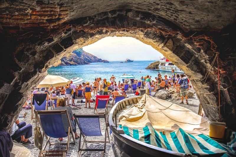 Crowded little beach in italy old seaview boathouse - stone arch - San Fruttuoso abbey - italian riviera - italy. San Fruttuoso, Italy, 29 Apr 2018 - old stock image