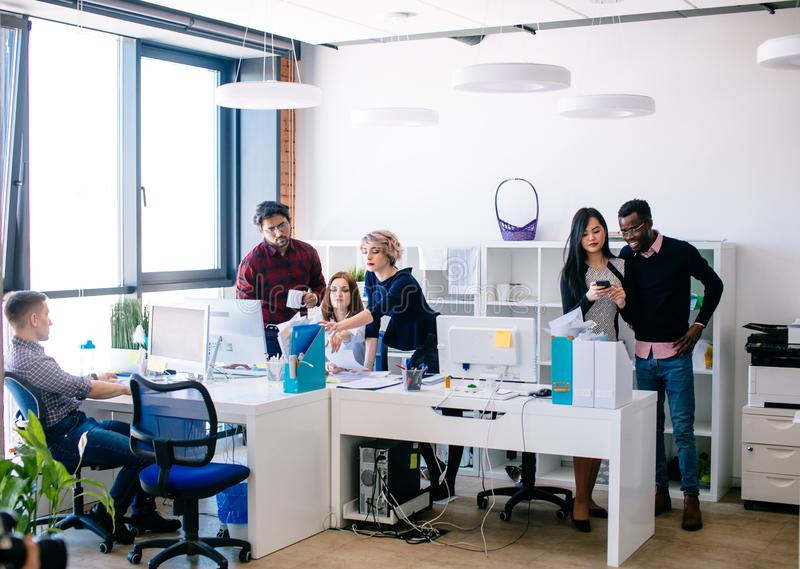Crowded office with young active employees. Everybody is doing his duties at workplace royalty free stock photos