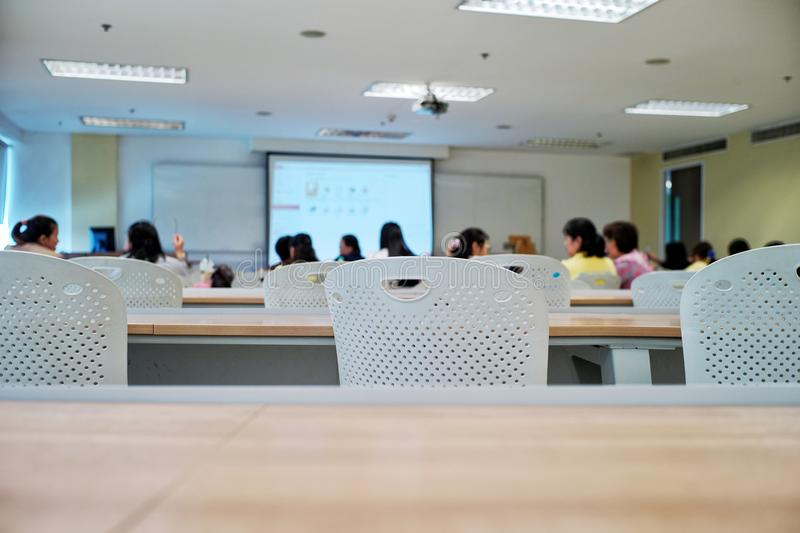 Crowded people attending the seminar event. Empty chairs in the classroom with blurred students in stock images