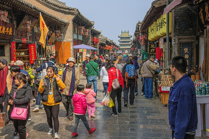 A crowded shopping street. Editorial: PINGYAO, SHANXI, CHINA, April 10, 2019 - A crowded shopping street in the old town of Pingyao stock photos