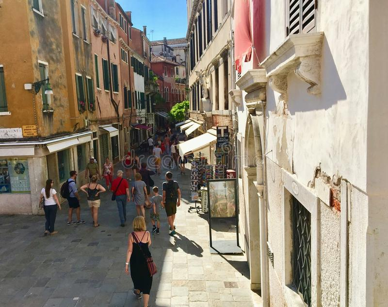 A crowded street full of tourists exploring the stores and restaurants surrounded by beautiful old Venetian architecture. Venice, Italy - June 30th, 2019: A royalty free stock image