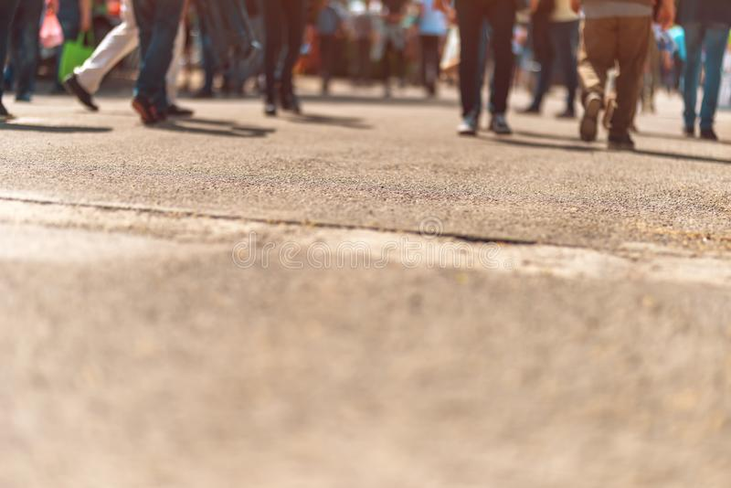 Crowded street and people walking. Low angle view on pedestrian legs with asphalt walkway as copy space, selective focus on portion of the road and the crowd stock image