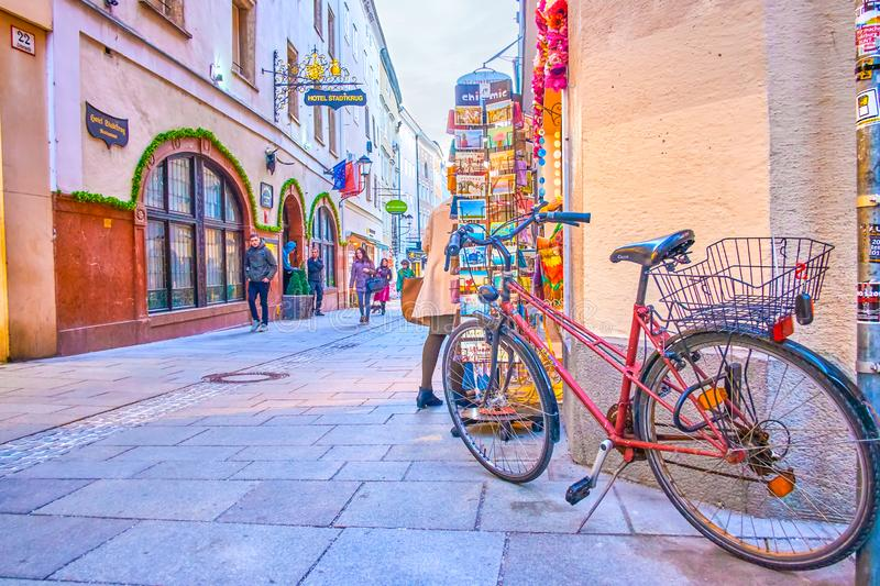 Crowded tourist street of Salzburg, Austria. SALZBURG, AUSTRIA - FEBRUARY 27, 2019: The parked bicycle at the postcard stand of souvenir store in crowded stock images