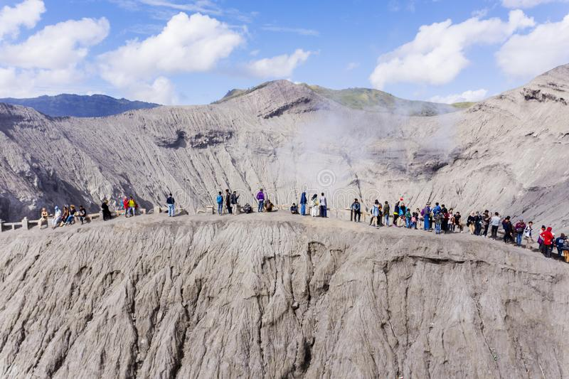 Crowded tourist visiting crater of Bromo volcano stock photography