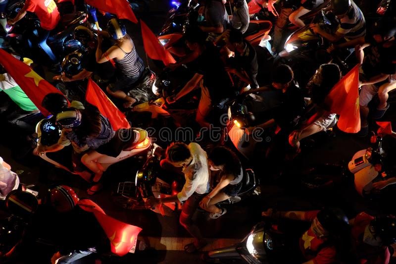Crowded Vietnamese street at night, young people ride motorbikes in traffic jam royalty free stock photography