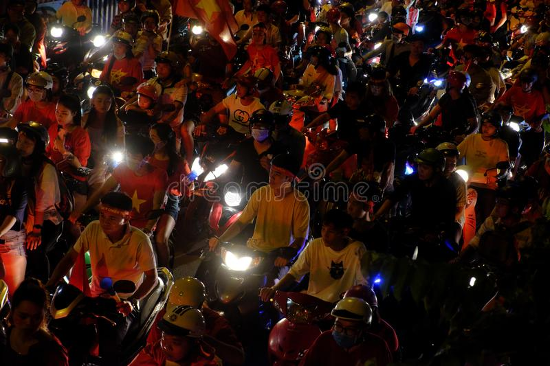 Crowded Vietnamese street at night, young people ride motorcycles in traffic jam stock photos