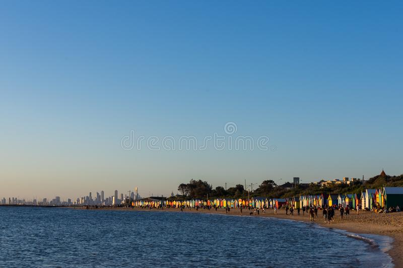 Crowds on busy Brighton Beach, site of many colourful bathing boxes royalty free stock images