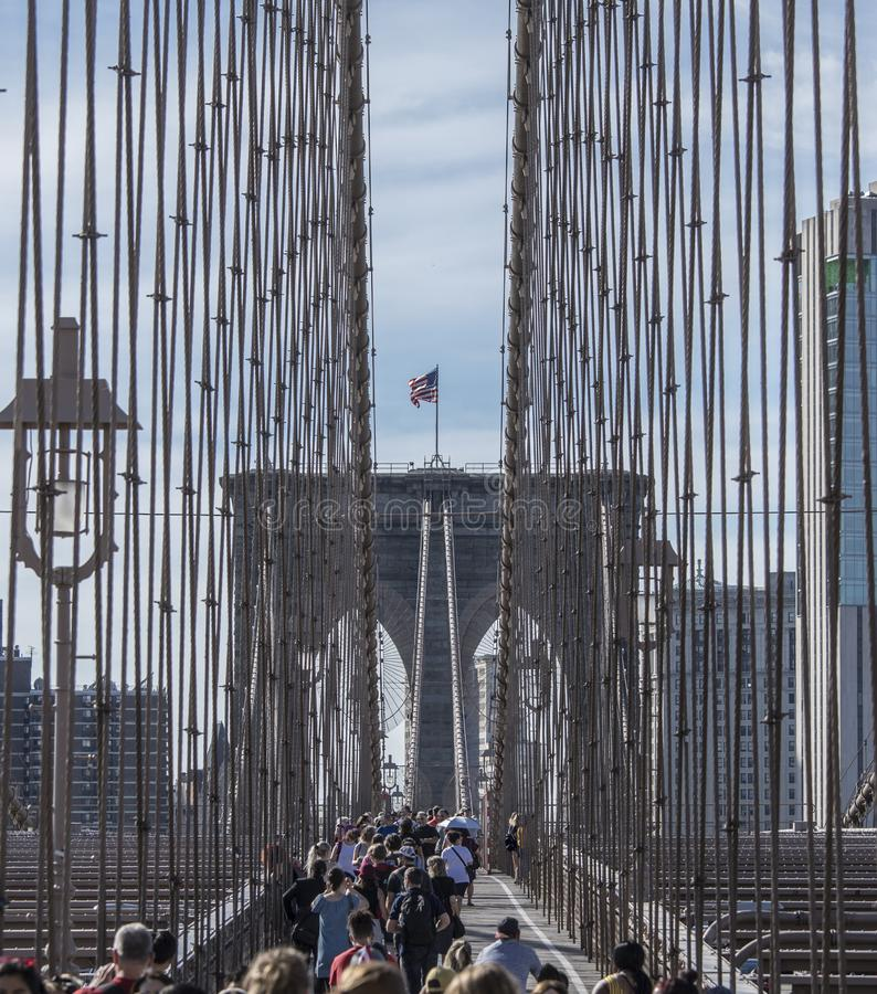 Crowds crossing the pedestrian walkway on the Brooklyn Bridge in New York City stock images