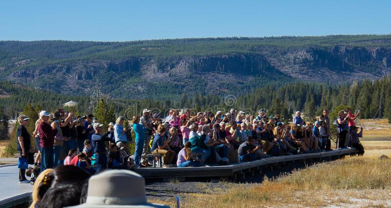 Crowds Gather to Watch Old Faithful Erupt in Yellowstone National Park. Crowds gather to watch the Old Faithful Geyser erupt in Yellowstone National Park royalty free stock photography