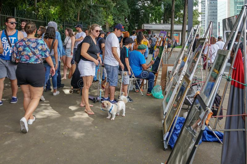 Crowds looking at painting in Paulista Avenue on Sunday afternoon. Paulista Avenue is closed for vehicles every Sunday. Sao Paulo, Brazil royalty free stock images