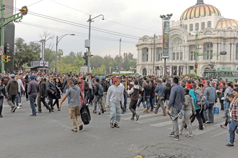 Crowds make their way past the Palacio de Bellartes in the historic center of Mexico City, Mexico stock photography