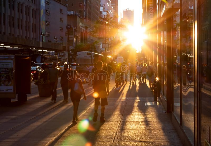 Crowds of people cast long shadows as they walk into the bright light of sunset on 34th Street in Midtown Manhattan New York City. New York City 2019: Crowds of stock photos