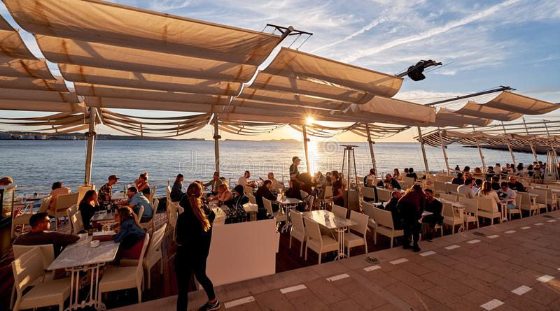 Crowds of people meet the sunset at the seafront terrace of Savannah cafe stock photography
