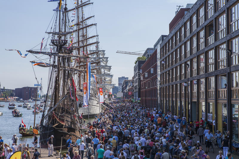 Crowds of people at Sail Amsterdam. Crowds of people walking past the parade of tallship which happens every 5 years in Amsterdam stock photography