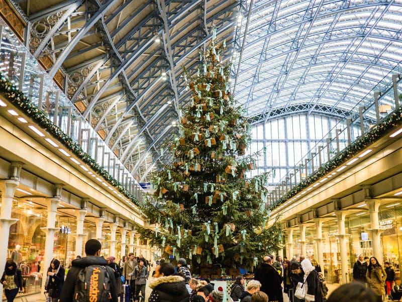 Crowds swirl around Christmas tree, St Pancras Station, London, UK. The majestic Christmas tree rises over the holiday crowds in St Pancras Station, Bloomsbury royalty free stock image
