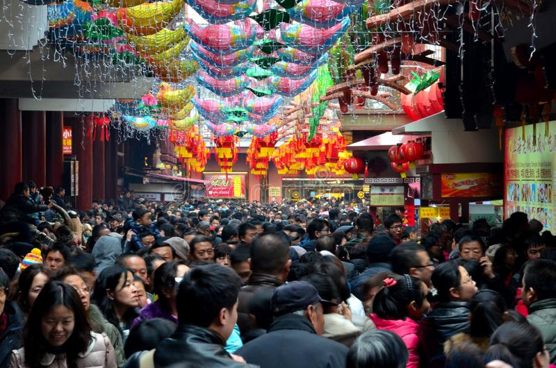 Crowds throng Shanghai Chenghuang Miao Temple over Lunar New Year China. Shanghai, China - February 13, 2013: Crowds pack a narrow lane inside Shanghai's famous stock images