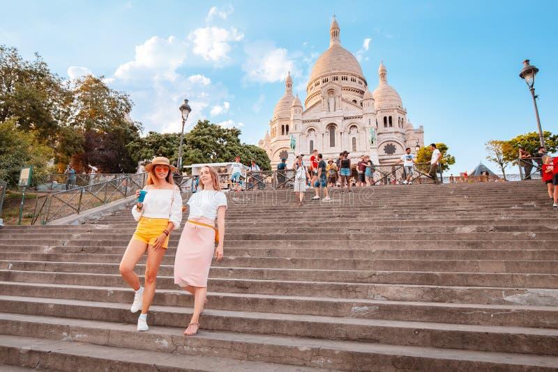 Crowds of tourists walking near Basilique du Sacre Coeur, on hilltop of Montmartre. Famous travel. 25 July 2019, Paris, France: Crowds of tourists walking near stock photos