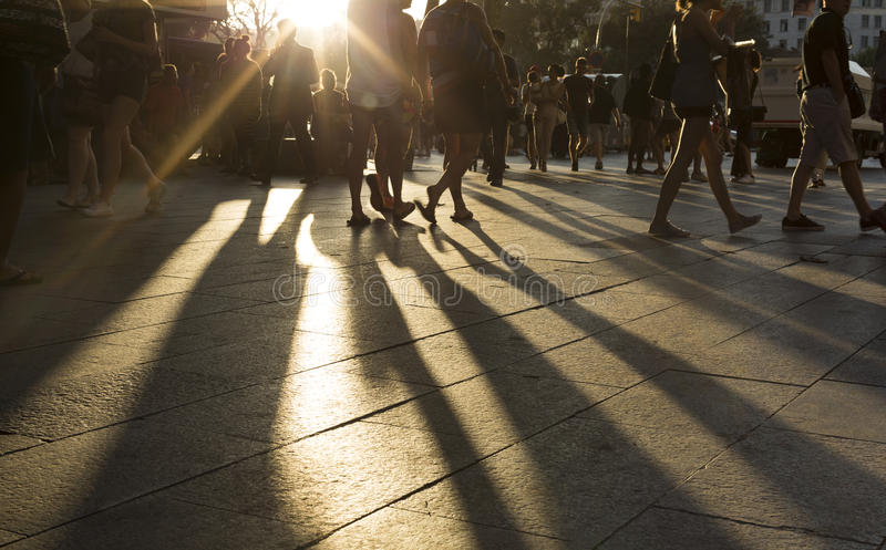 Crowds walking in a busy district as the sun flares between them in the late afternoon royalty free stock image