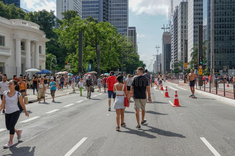 Crowds walking and looking at performances in Paulista Avenue on Sunday afternoon. Paulista Avenue is closed for vehicles every Sunday. Sao Paulo, Brazil royalty free stock image