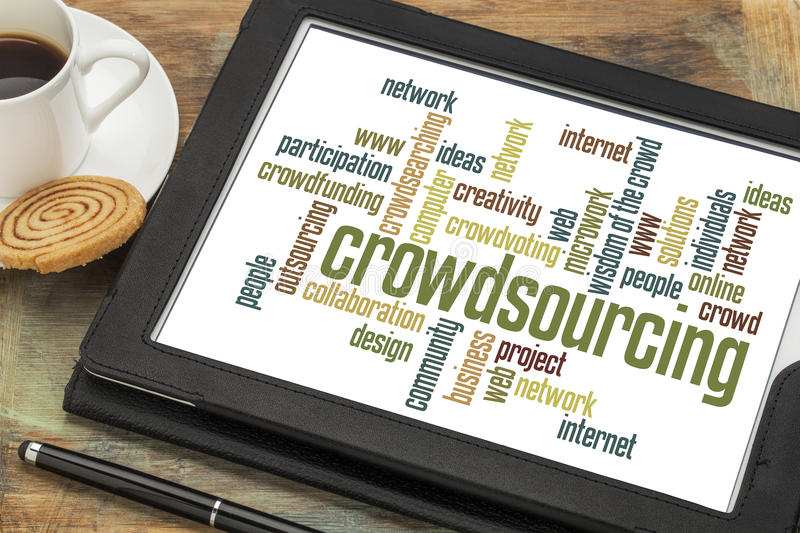 Crowdsourcing word cloud. On a digital tablet with a cup of coffee royalty free stock photography