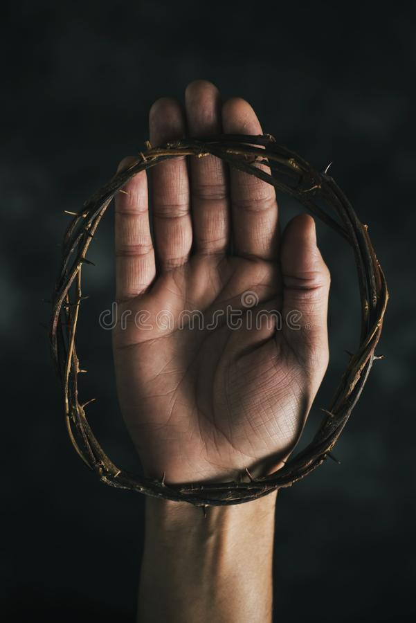 Crown of thorns on the hand of a man. High angle view of a crown of thorns on the hand of a man, on a dark background royalty free stock photography