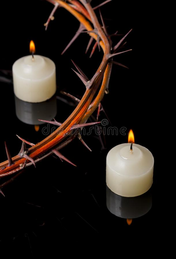 Crown of thorns of Jesus Christ at candles lights. Mirroring on black background royalty free stock images