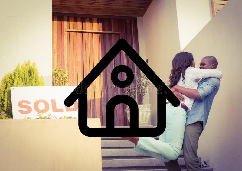 crrying他的妻子的丈夫反对房子概述在背景中 库存照片