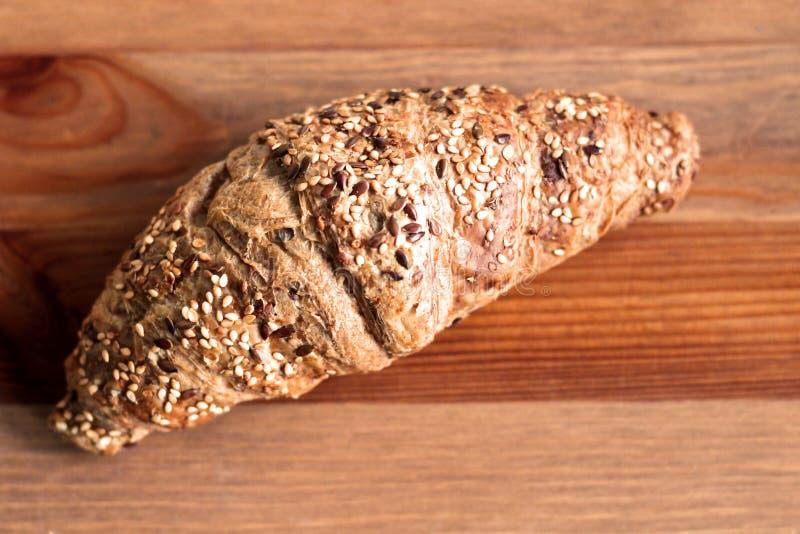Cruasán cocido con los granos blancos y negros del sésamo, fondo de madera del pan de levadura Fondo enmascarado Concepto de fres fotografía de archivo