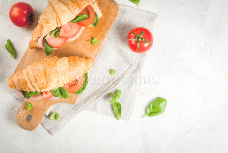 Cruasán con el jamón, el queso, los tomates frescos y la albahaca foto de archivo libre de regalías