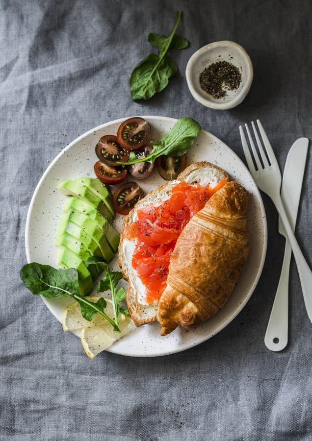 Cruasán con el queso cremoso y salmón ahumado, tomates del aguacate y de cereza deliciosos - desayuno equilibrado, brunch o bocad imagenes de archivo