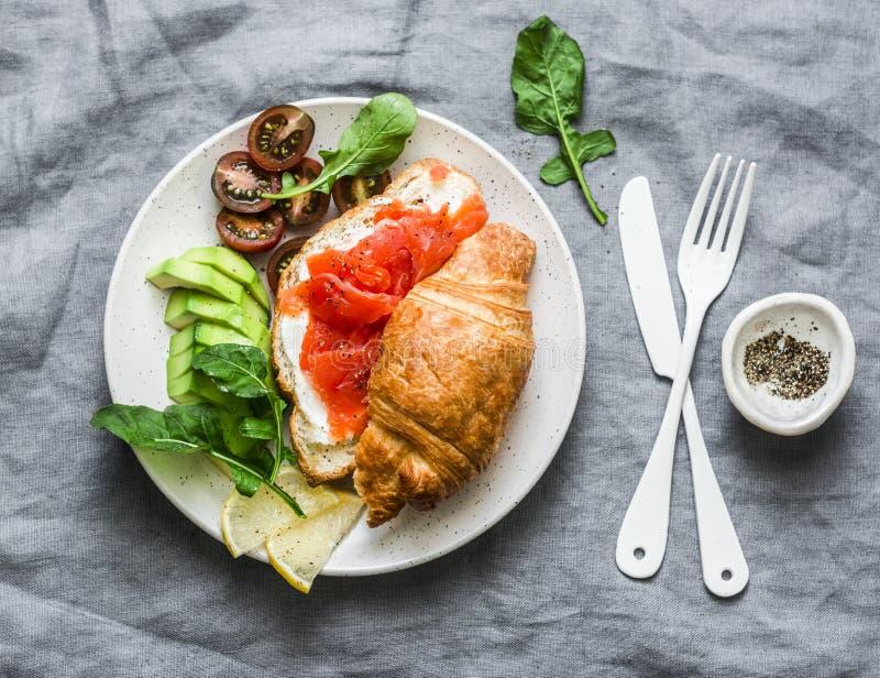Cruasán con el queso cremoso y salmón ahumado, tomates del aguacate y de cereza deliciosos - desayuno equilibrado, brunch o bocad imagen de archivo