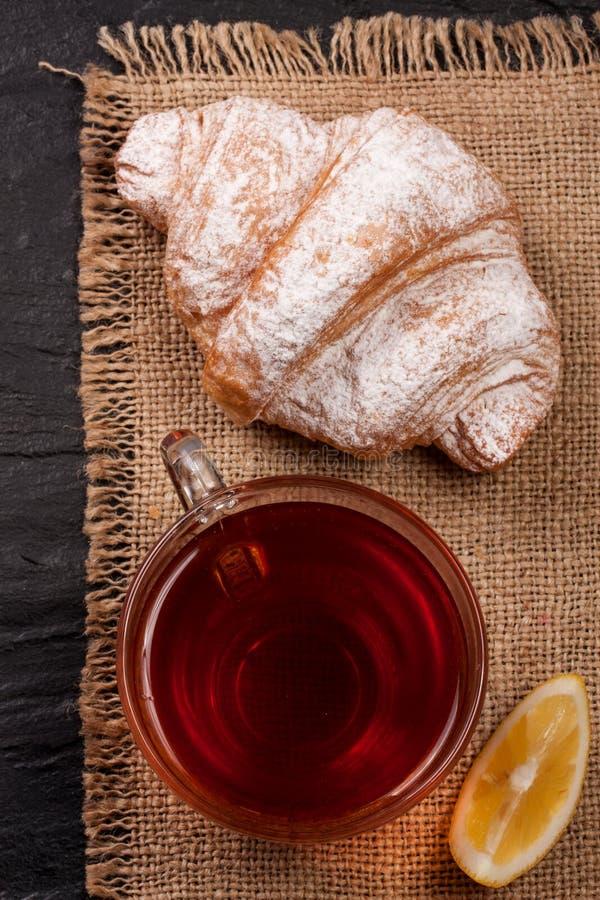 Cruasán con una taza de té en harpillera Visión superior imagenes de archivo