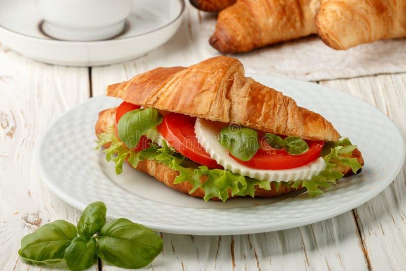 Cruasán del bocadillo del desayuno con queso, los tomates y la albahaca Caprese foto de archivo libre de regalías