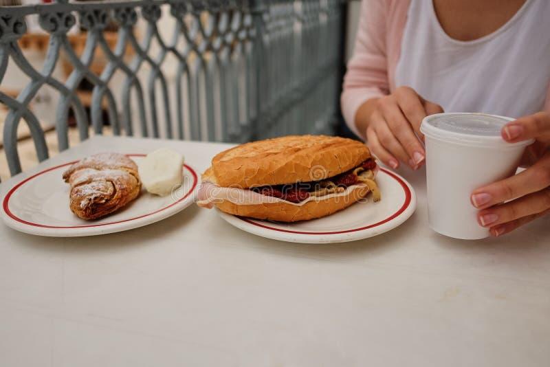 Cruasán ligero y caluroso del desayuno de la primavera con el jamón, queso, tomates frescos en una tabla blanca imágenes de archivo libres de regalías