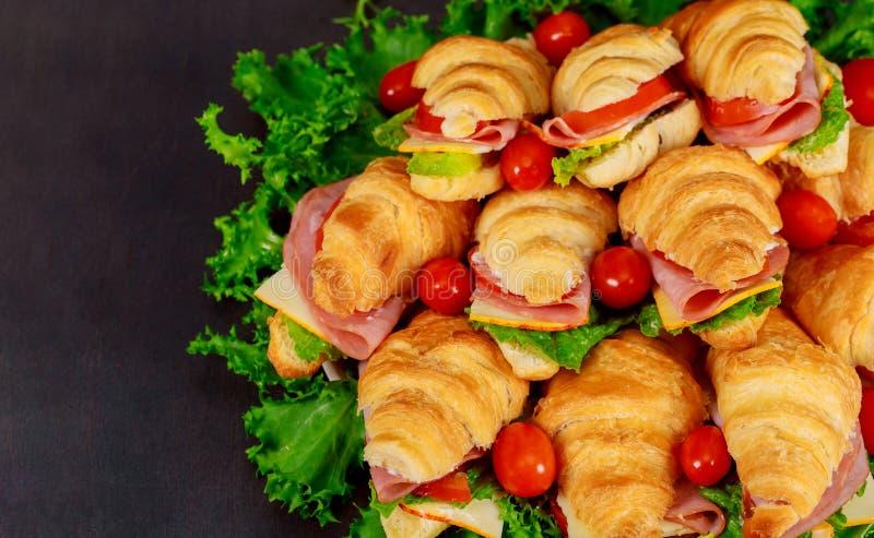 Cruasán o bocadillo fresco con la ensalada, jamón, jamon, tomates en fondo de madera fotografía de archivo