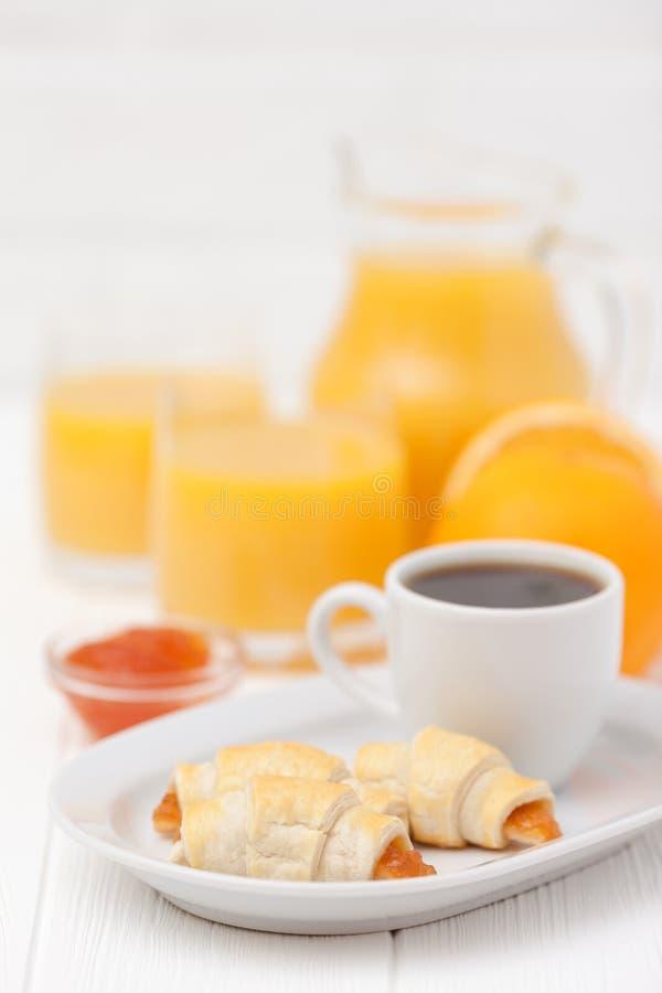 Cruasán recientemente cocido, zumo de naranja, atasco, taza de café sólo en el fondo de madera blanco Galleta hecha en casa fresc imagen de archivo
